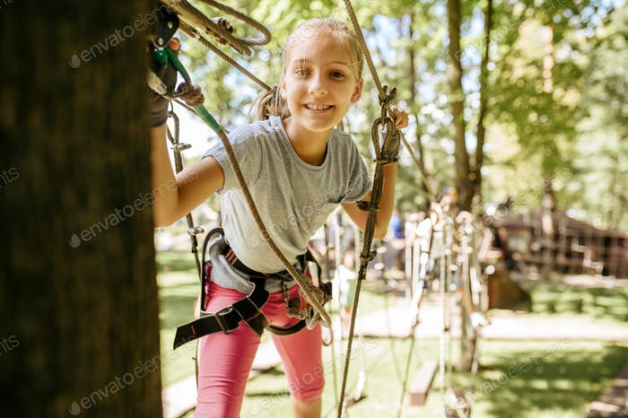 Smiling girl climbs in rope park, playground