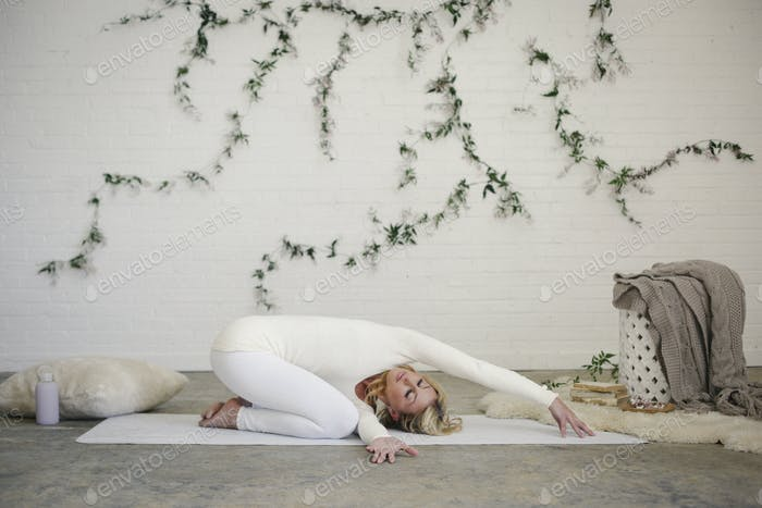 A blonde woman kneeling on a yoga mat in a pose.