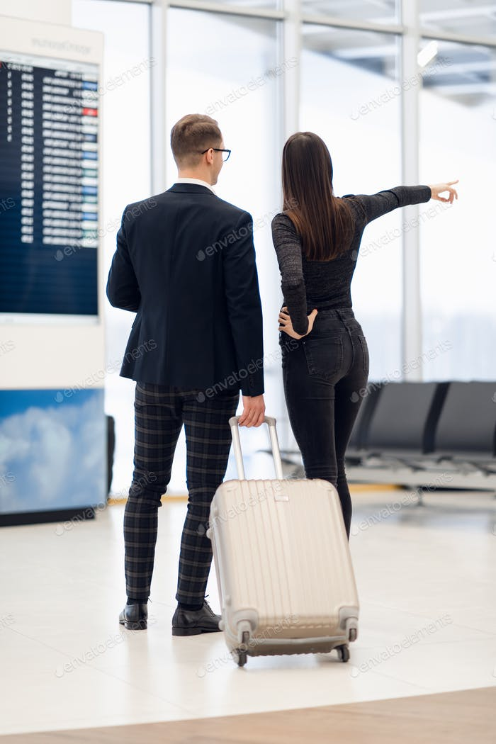 Young couple in an airport about to take a plane, looking timetables