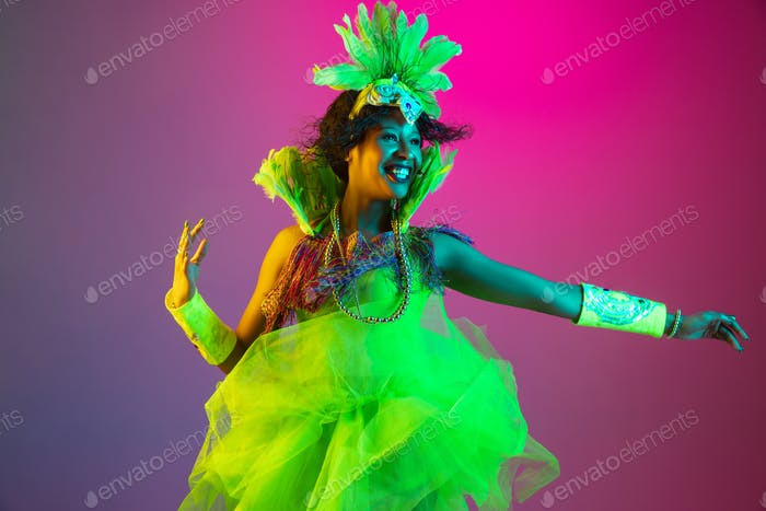 Beautiful young woman in carnival and masquerade costume on gradient studio background in neon light