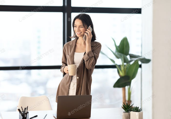 Girl talking on cell phone at office holding mug