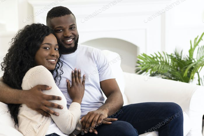 Married couple sitting at home posing to camera