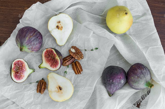 Figs, pears and pekan nuts on a white tissue on a wooden table s