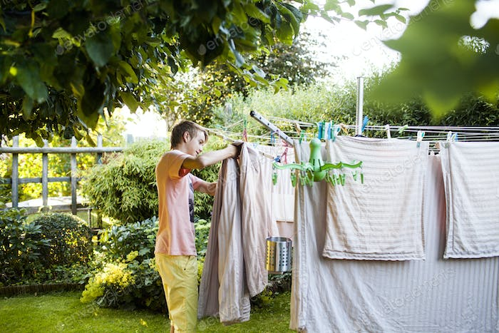 Teenage boy doing laundry work in garden