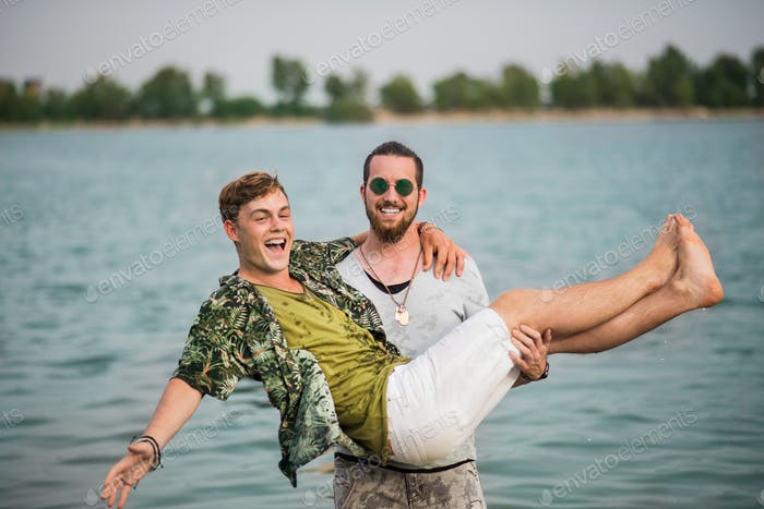 Young men friends having fun at summer festival, standing in lake.