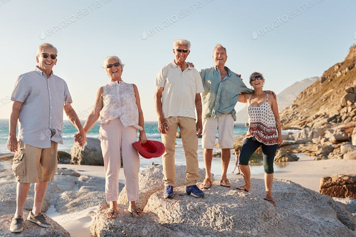 Portrait Of Senior Friends Standing On Rocks By Sea On Summer Group Vacation