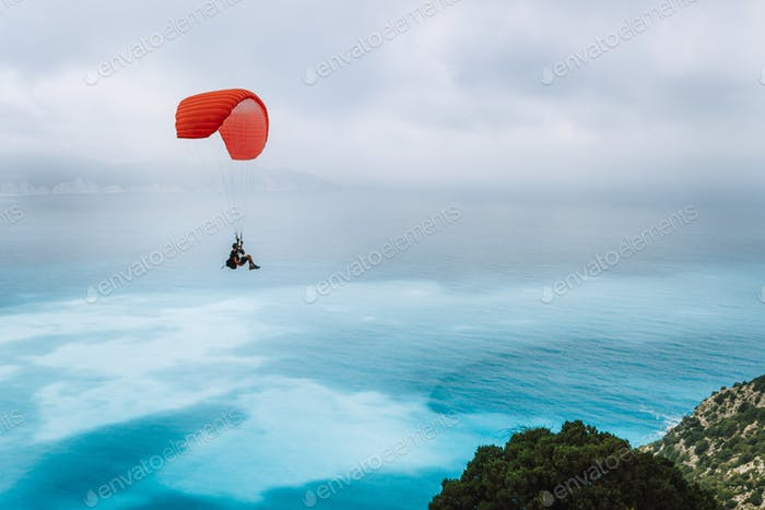 Paraglider against blue sea with foggy clouds. Kefalonia island, Greece. recreation hobby activity