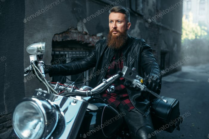 Motorcyclist in leather jacket poses on chopper