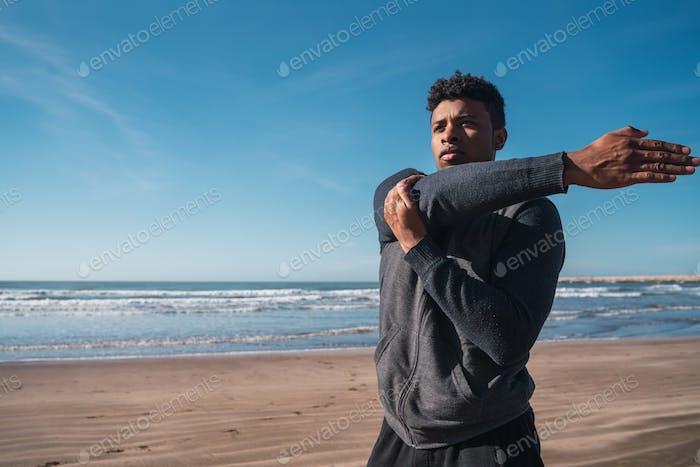 Athletic Mann Stretching Arme vor dem Training.