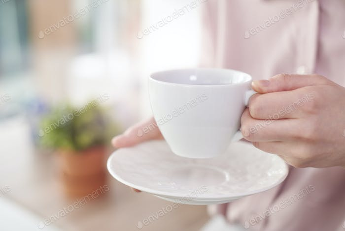 Human hand holding white cup with saucer