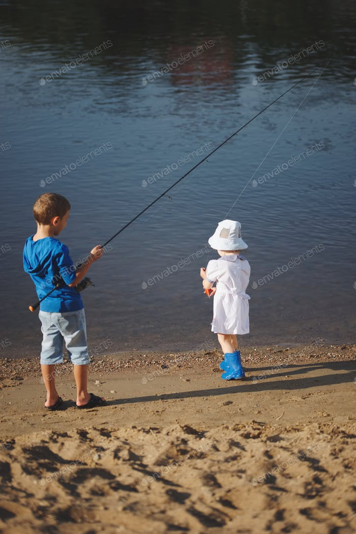 boy and girl with rod on coast of river