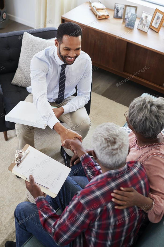 Senior Couple Shaking Hands With Male Financial Advisor At Home