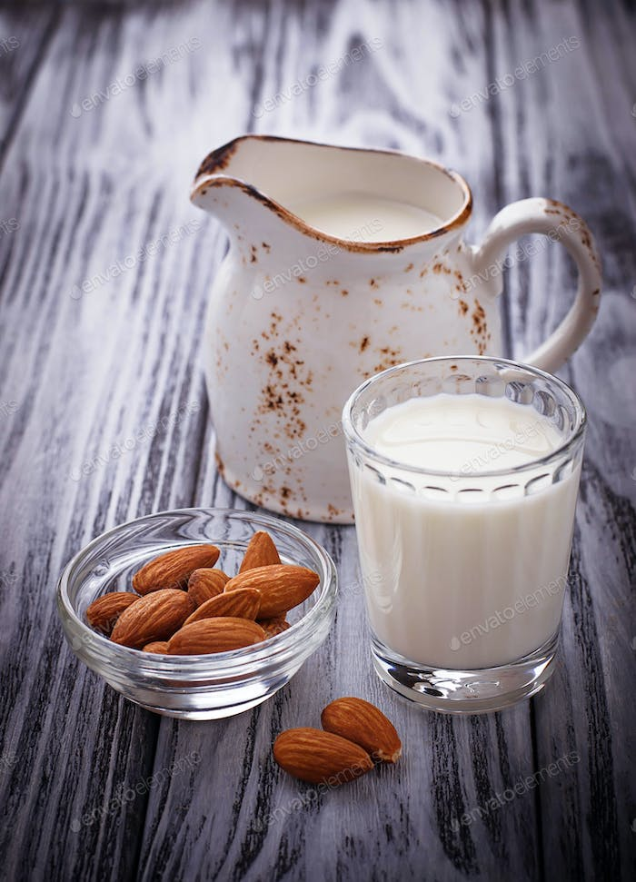 Almond milk and almonds on wooden background