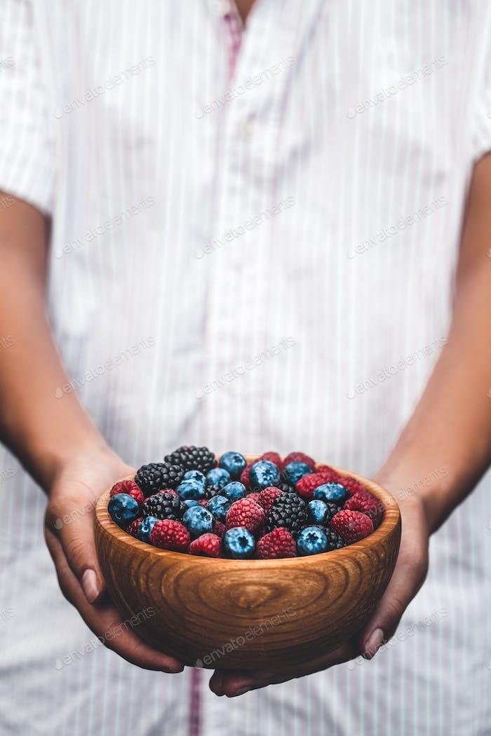 Halten Sie einen Teller voller Beeren. Frühstücks-Mix. Himbeeren, Heidelbeeren, Brombeeren. Teller