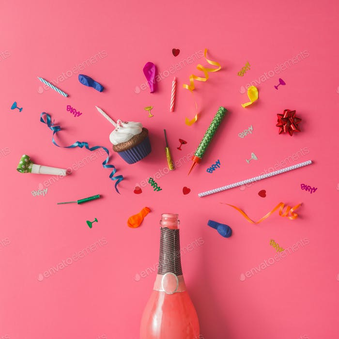 Champagnerflasche mit bunten Partyartikeln auf rosa Hintergrund. Flache Lag.