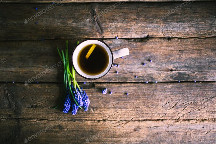 Blue flowers and cup of tea on wooden background. Vintage