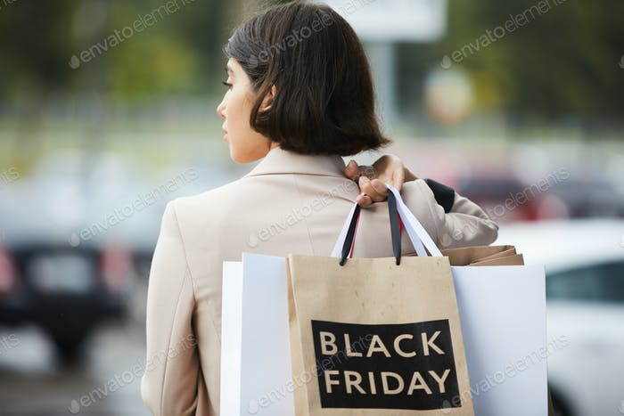 Young Woman Leaving Boutique Back View