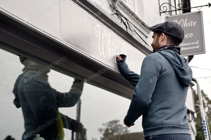 A man on a ladder fixing a painted name sign onto a bracket on a shopfront.