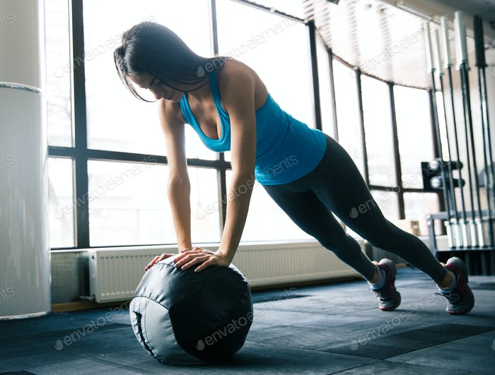Cute young woman working out with fit ball