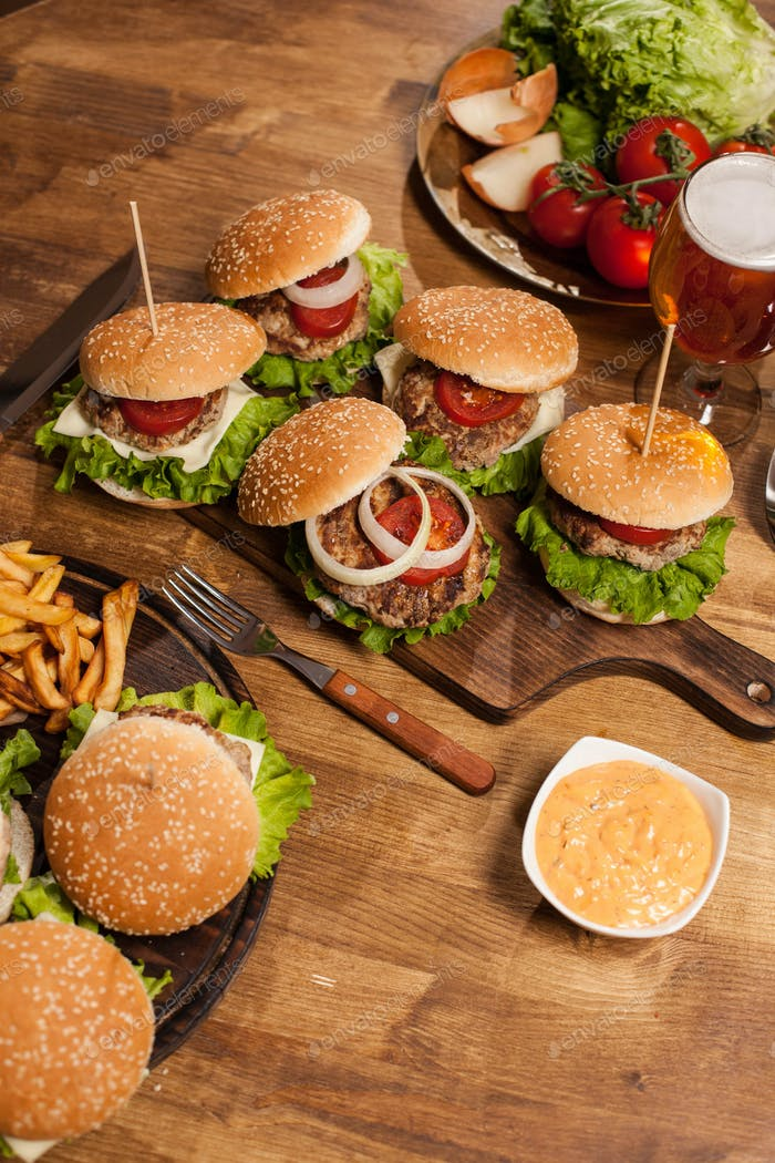 Classic burgers on wooden cutting board next to red tomatoes