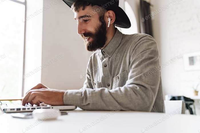 Photo of pleased young man using laptop and earpods while sitting