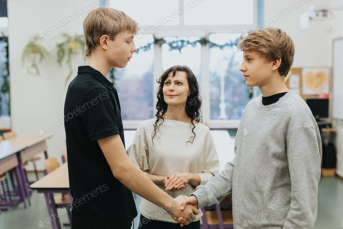 Teacher talks at school with two conflicted teenage boys