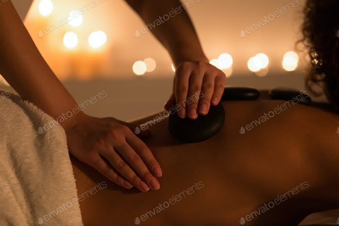 Woman getting hot stones back massage in spa salon