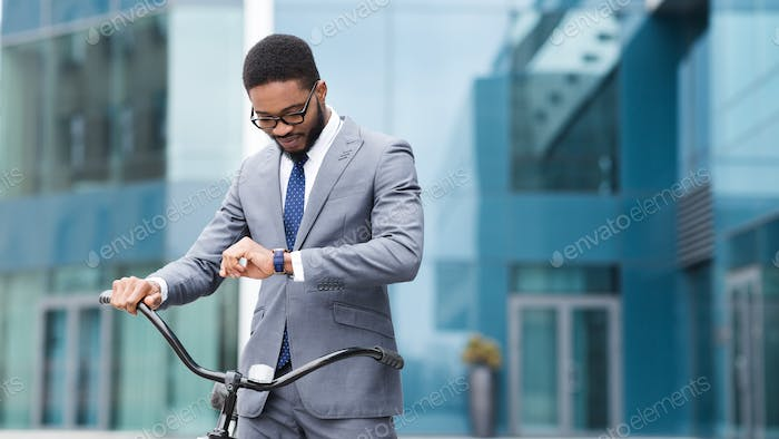 Handsome black manager checking time on wristwatch