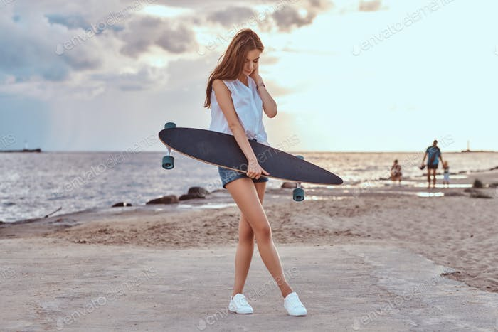 Brunette girl with a skateboard on the beach in cloudy weather during sunset.