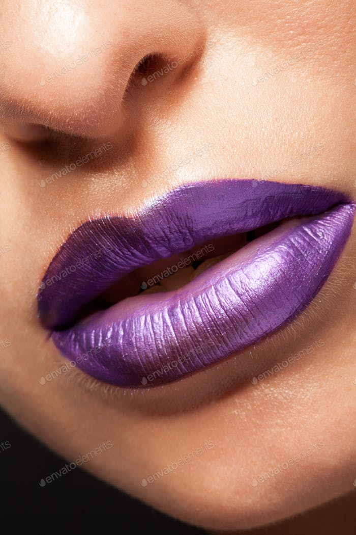Close up view of beautiful woman lips with mat purple lipstick