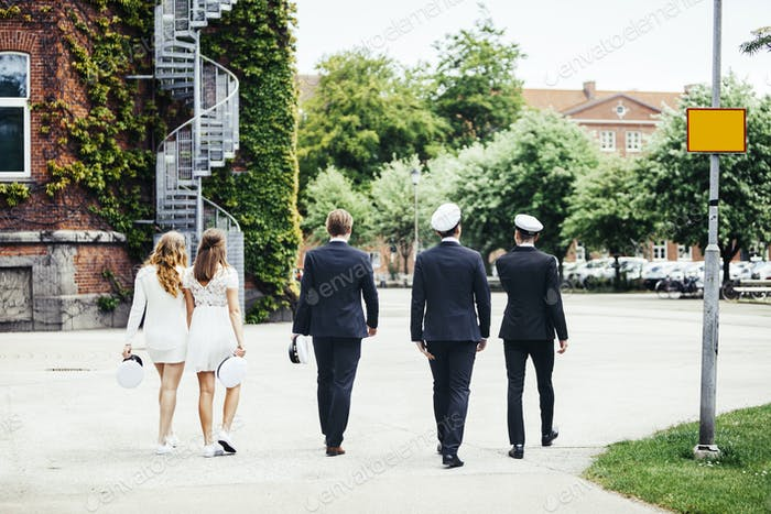 Rear view of male and female graduates walking on footpath at campus