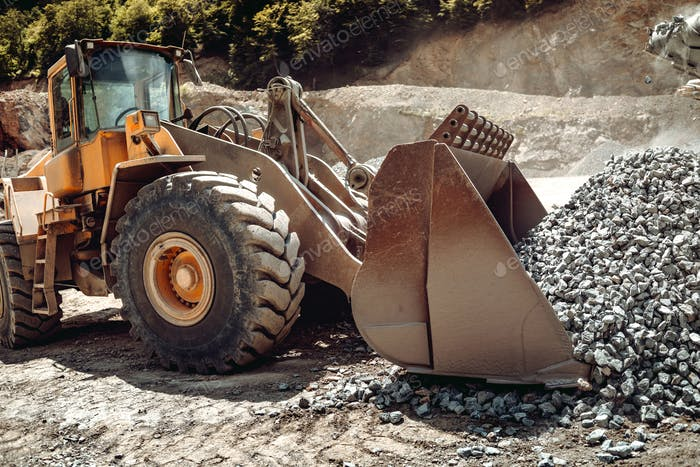 Close up of wheel loader loading gravel and sand materials