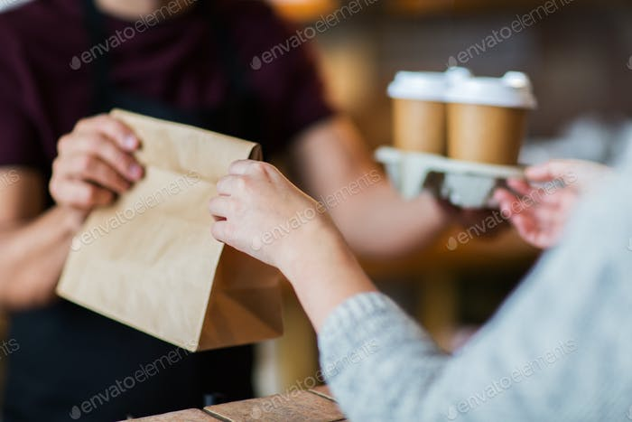man or bartender serving customer at coffee shop