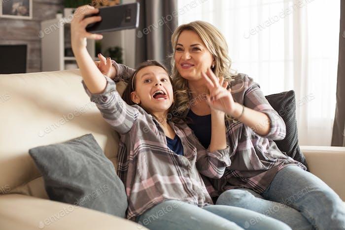 Lustige kleine Tochter und Ihre Mutter sind nehmen ein selfie