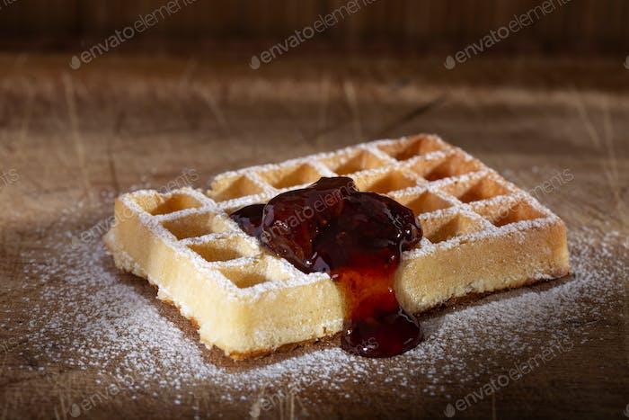 Belgian cake waffle with strawberry jam and powder sugar