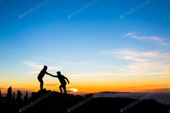 Teamwork Paar Klettern helfende Hand