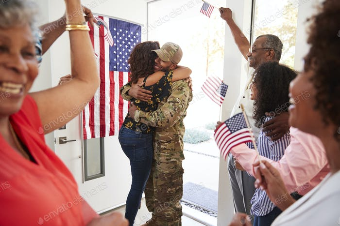 Millennial woman and family welcoming young black male soldier home, embracing in doorway, close up