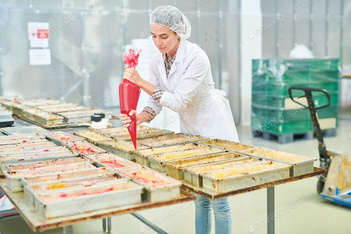 Confectionery factory worker squeezing pastry bag