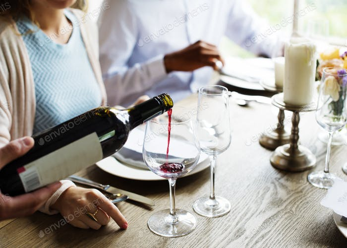 Waiter Poring Serving Red Wine to Customers in a Restaurant