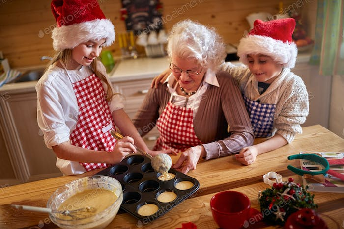 children enjoying with grandmother making Christmas cookies