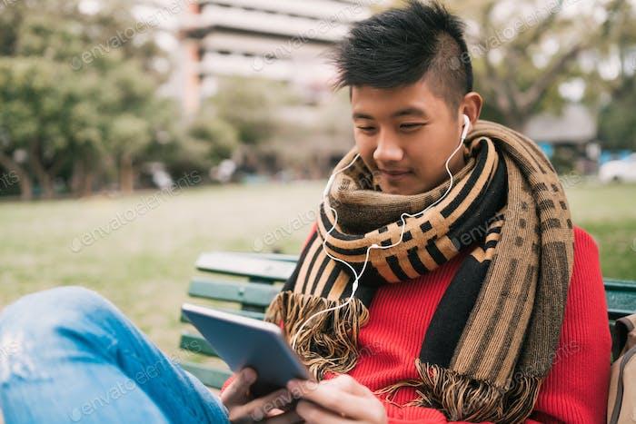 Asian man using his digital tablet.
