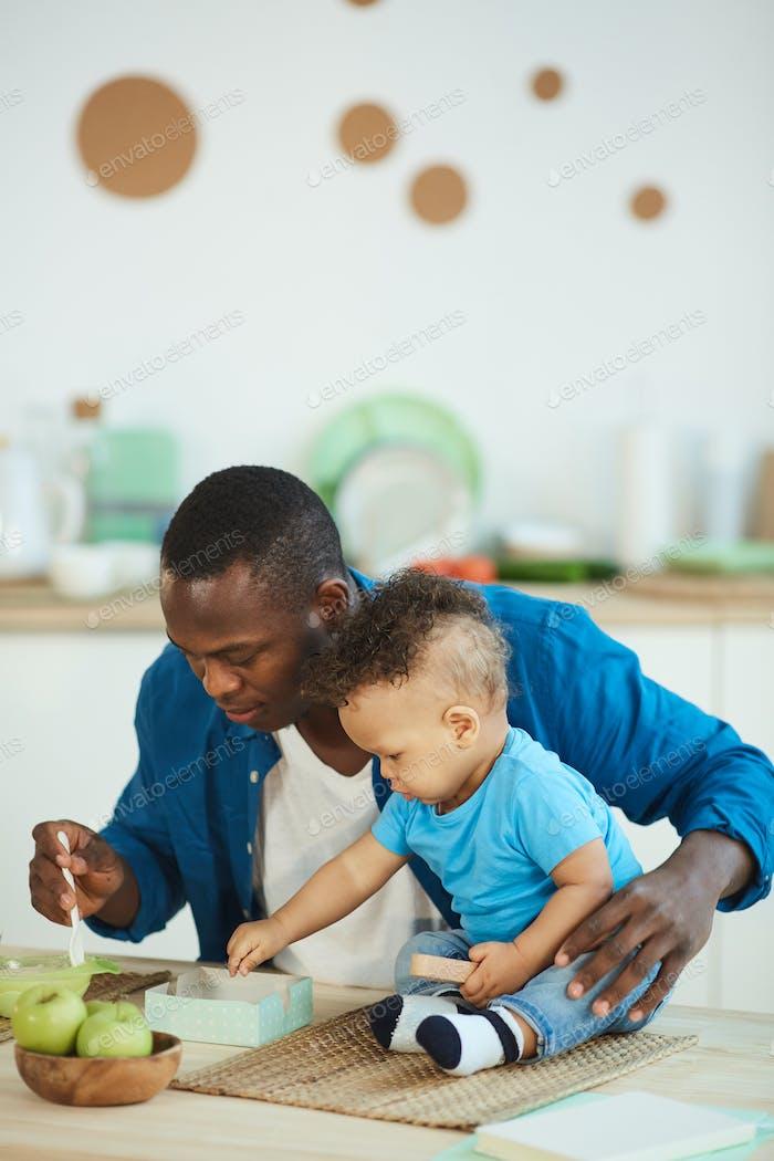 Father Feeding Son Apple Puree
