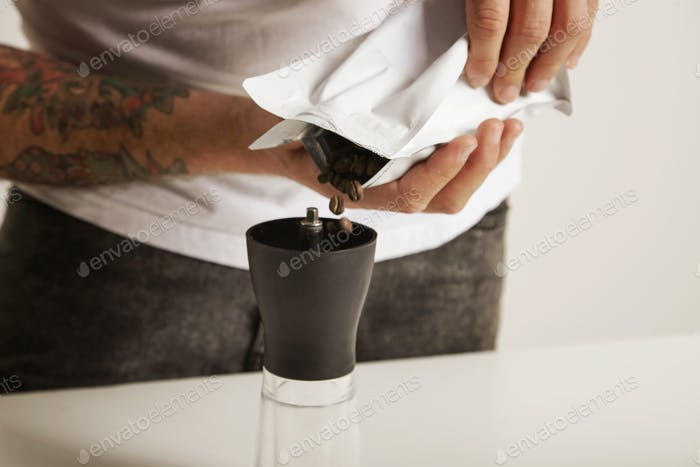 Pouring coffee beans into  grinder