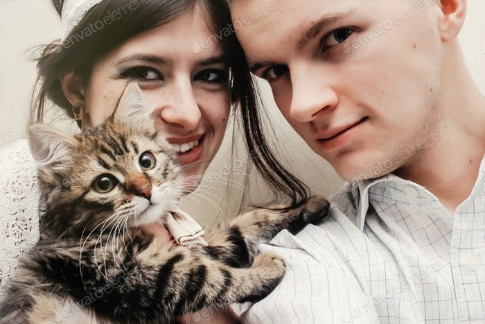 beautiful couple with cute funny kitten with bow tie