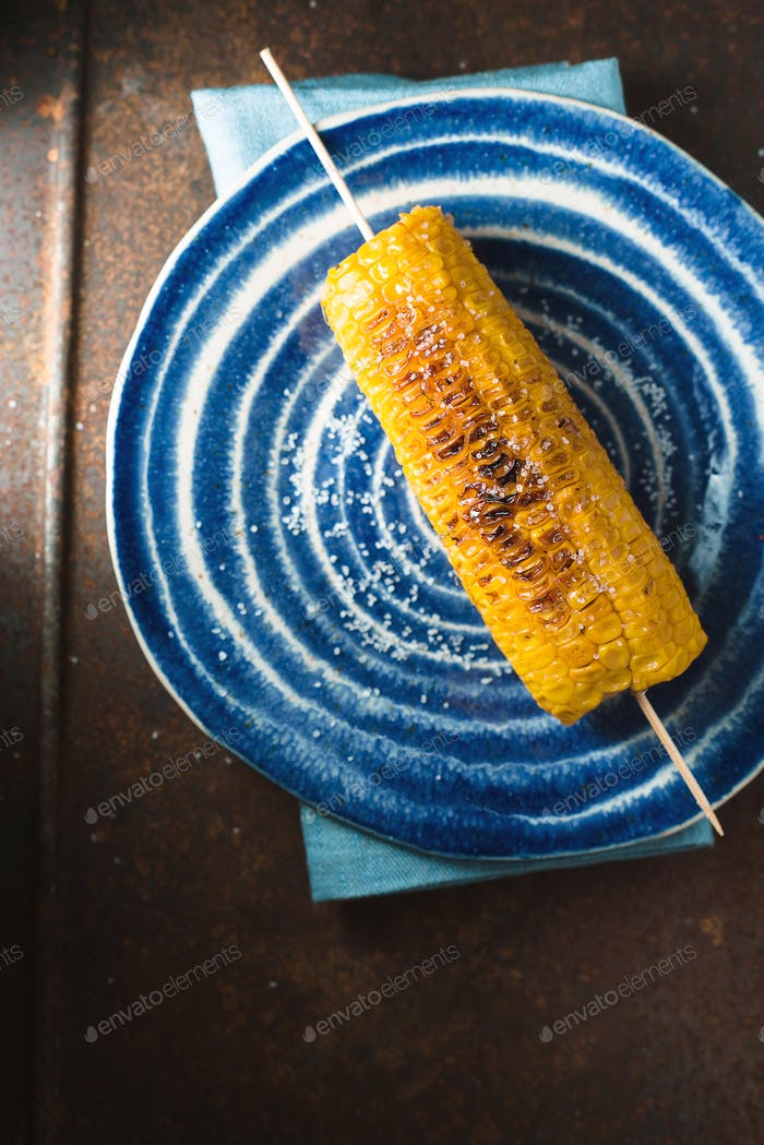 Roasted corn with salt on a blue plate and a napkin