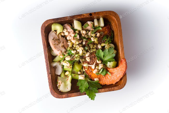 Vegetable salad with quail eggs in a wooden bowl on a white background
