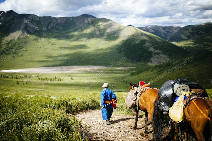 Guides and travelers ride horses into the East Taiga forests of northern Mongolia to visit the