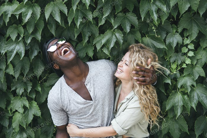 mixed race couple hugging in nature