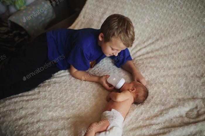 boy feeding newborn baby with bottle of milk