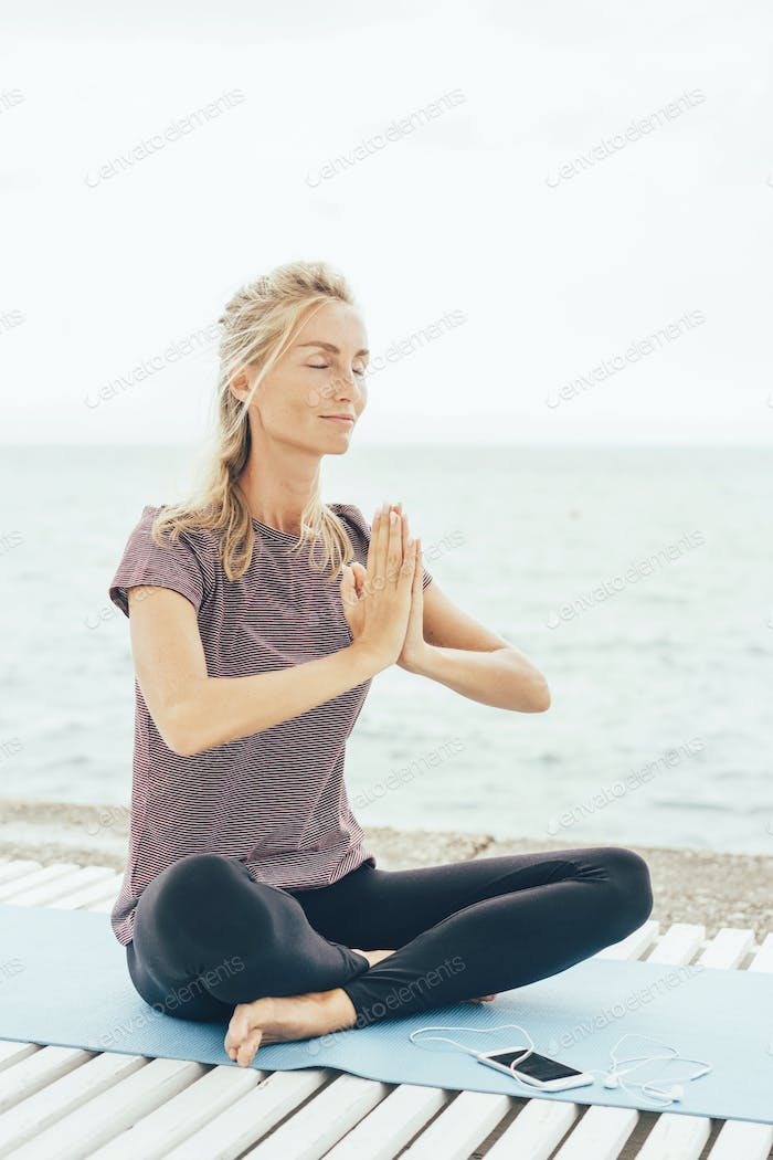 Caucasian woman in lotus position greets the namaste before starting yoga practice. Sports concept.